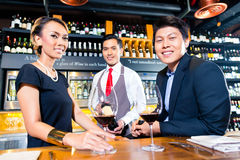 Asian couple tasting red wine in bar Royalty Free Stock Images