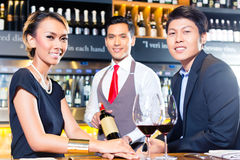 Asian couple tasting red wine in bar Stock Photo