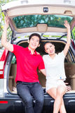 Asian couple with their new car being excited Stock Photo