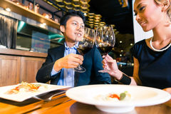 Asian couple toasting with red wine. Asian couple toasting in restaurant Royalty Free Stock Photography