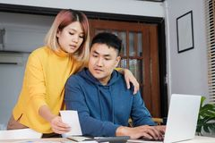 Asian couple together calculate home budget with paper bill and laptop in new house at table in kitchen stock photos