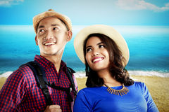 Asian couple travel along on the beach Stock Photo
