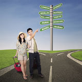 Asian couple travel with road signs outdoor Royalty Free Stock Photos