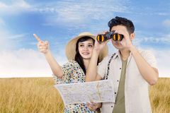 Asian couple using binoculars in field. Asian couple is using binoculars in wheat field Royalty Free Stock Image