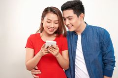 Asian couple using cell smart phone message smile standing on white background.  royalty free stock images