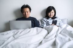 Asian couple using digital devices in bed Royalty Free Stock Photos