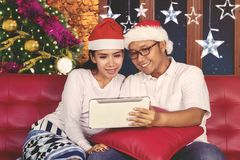 Asian couple using tablet at Christmas time Royalty Free Stock Photos