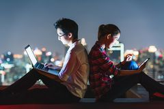 Asian couple using laptop and smartphone together, lean on each other on rooftop at night. Young Asian couple using laptop and smartphone together, lean on each Stock Photo