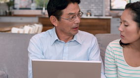Asian couple using laptop on sofa stock video footage