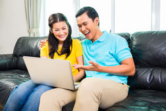 Asian couple using laptop on sofa Royalty Free Stock Photos
