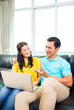 Asian couple using laptop on sofa Stock Photo