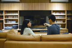 Asian couple using a remote control to turn on TV with blank screen stock photography