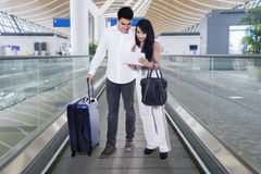 Asian couple using tablet on the airport escalator Royalty Free Stock Photography