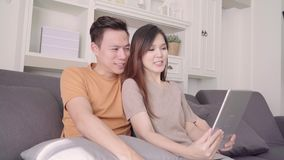 Asian couple using tablet VIDEO Call with friend in living room at home.