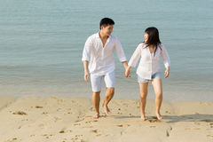 Asian couple walking on the beach. Stock Image