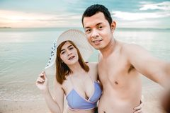Couple on the Beach. Asian couple walking on the beach when the sun is about to set the time and day honeymoon, both are selfie Royalty Free Stock Photos