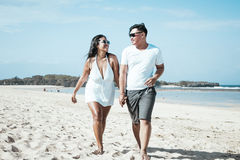 Asian couple walking on the beach of tropical Bali island, Indonesia. Stock Photos