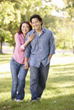Asian couple walking hand in hand in park Stock Photos