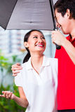 Asian couple walking with umbrella through rain Royalty Free Stock Image