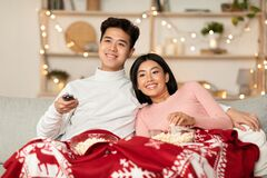 Free Asian Couple Watching Christmas Movies On TV Sitting At Home Royalty Free Stock Photography - 197513667