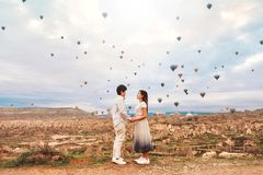 Asian couple watching colorful hot air balloons flying over the valley at Cappadocia, Turkey This Romantic time of love