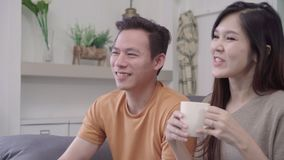Asian couple watching TV and drinking warm cup of coffee in living room at home, sweet couple enjoy love moment. stock video
