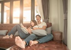 Asian couple watching TV sitting on a couch at home cheerful royalty free stock photo