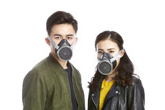 Asian couple wearing gas mask. Young asian couple wearing gas mask staring at camera, isolated on white background Royalty Free Stock Images