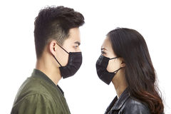 Asian couple wearing mask staring at each other. Young asian men and women wearing black mask staring at each other, isolated on white background Stock Image