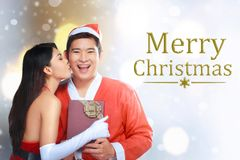 Asian couple wearing santa costume holding banner Stock Photos
