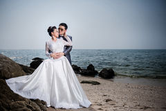 Asian couple wearing wedding dress and suit. For beach wedding ceremony. Couple on the beach concept. White bridal dress royalty free stock photography