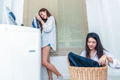 Asian couple women doing housework and chores in front of washing machine and loading clothes in laundry room together. People. And daily life concept stock photography
