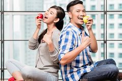 Asian couple having apples as healthy snack. Asian couple, women and man, having apples as healthy snack in their urban flat Royalty Free Stock Image