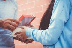 Asian couple young man giving gift to woman outdoors. Royalty Free Stock Images