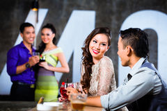 Asian couples flirting and drinking at nightclub bar. Two Asian young and handsome party people couples flirting and drinking at the bar in luxurious and fancy Stock Image
