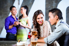 Asian couples flirting and drinking at nightclub bar Royalty Free Stock Images