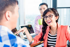 Asian creative agency workers discussing Royalty Free Stock Photo