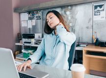 Asian creative designer woman catch her neck pain from hard work royalty free stock photo