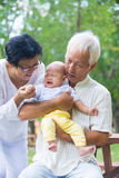 Asian crying baby comforted by grandparents Royalty Free Stock Images