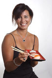 Asian Cuisine. A woman holding a tray of sushi, looking at the camera and smiling Stock Photography