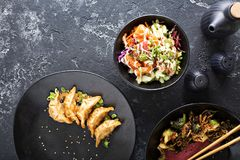 Asian cuisine dishes on the table overhead view. Asian cuisine dishes with poke bowl, fried potstickers and sesame brussel sprouts on the table overhead view royalty free stock photo
