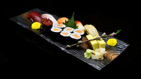 Asian cuisine or Japanese food. Sushi medium set on wooden plate Royalty Free Stock Image