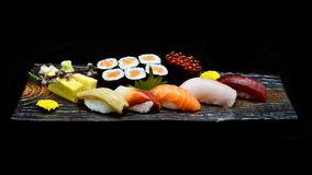Asian cuisine or Japanese food. Sushi medium set on wooden plate Stock Images