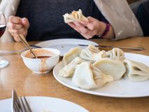 Asian cuisine. National Georgian food khinkali with Satsebeli sauce. Girl hand holding khinkali. Tbilisi, Georgia.  stock photography