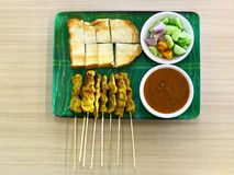 Asian Cuisine, Pig Satay or Moo Satay with toast on green dish and wood table. Asian Cuisine, Pig Satay or Moo Satay on white dish stock photo