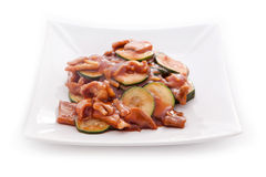 Asian cuisine zucchini with mushrooms. Vegetables in spicy sauce, zucchini, onions, mushrooms on a plate on a white background Stock Images