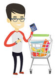Asian customer counting on calculator. Asian man standing near supermarket trolley with calculator in hand. Man checking prices on calculator. Customer counting Royalty Free Stock Photography