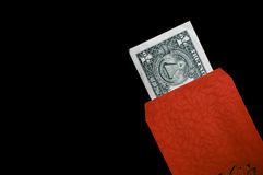 Asian Customs- Lucky Red Envelope. A lucky red envelope with a stingy 1 dollar bill given during chinese neew year and special events Royalty Free Stock Photos