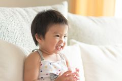 Asian cute baby girl smiling and holding a glass of water. Concept of a healthy lifestyle. stock images