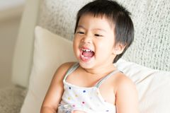 Asian cute baby girl smiling and holding a glass of water. Conce royalty free stock photography